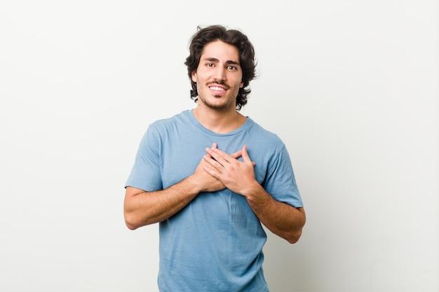 Beau jeune homme contre un mur blanc a une expression amicale, appuyant la paume contre la poitrine. concept d'amour.