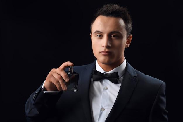 Beau jeune homme en costume à l'aide de parfum sur fond noir
