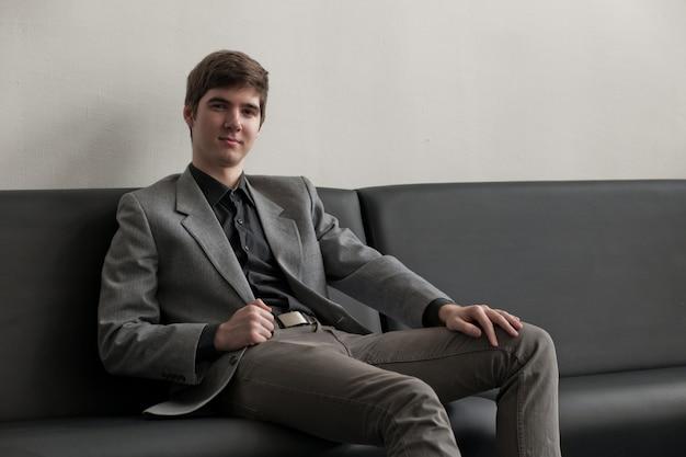 Beau jeune homme en costume assis sur un canapé à la réception.