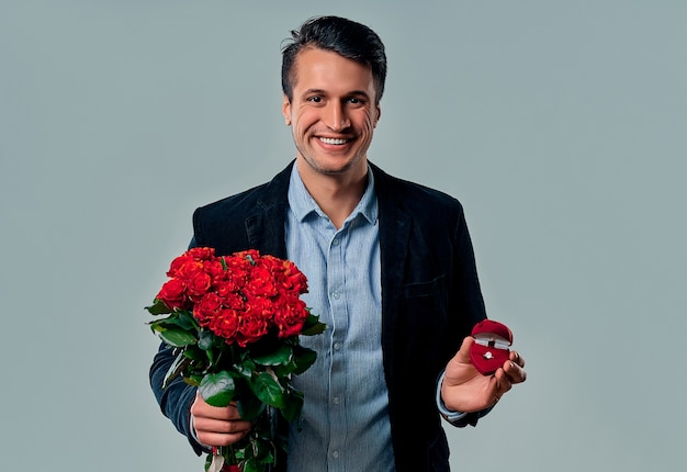 Beau jeune homme en costume pose sur gris avec anneau et roses rouges dans les mains, regardant la caméra et souriant.