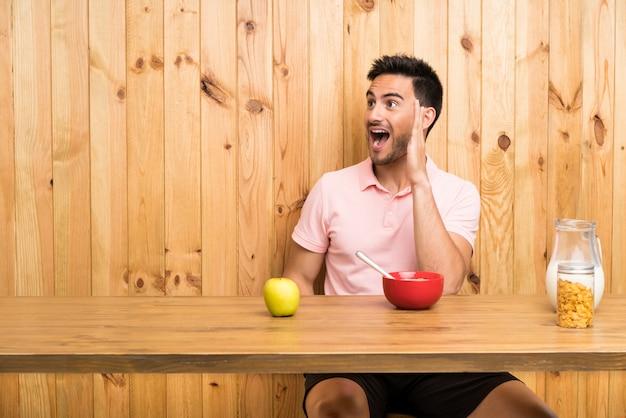 Beau jeune homme dans une cuisine prenant son petit déjeuner en criant avec la bouche grande ouverte