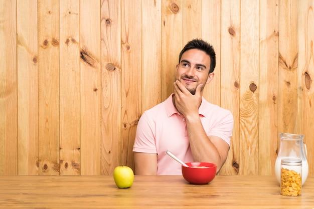 Beau jeune homme dans une cuisine prenant son petit déjeuner en pensant à une idée