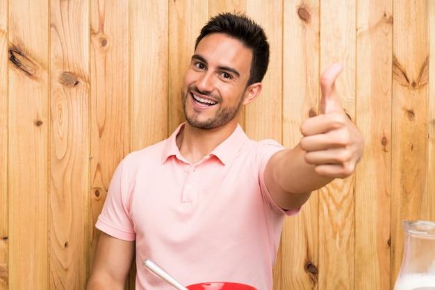 Beau jeune homme dans une cuisine prenant son petit déjeuner avec les pouces levés parce qu'il s'est passé quelque chose de bien