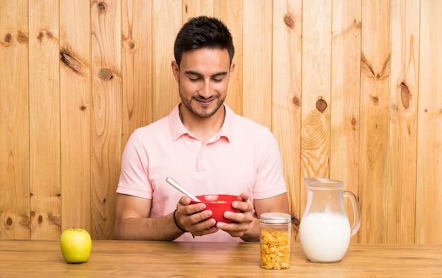 Beau jeune homme dans une cuisine prenant son petit déjeuner