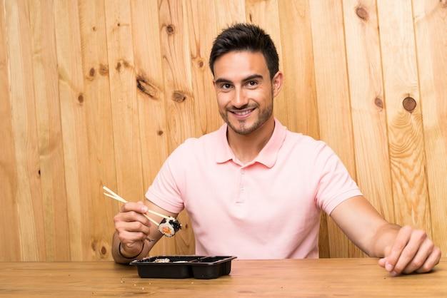 Beau jeune homme dans une cuisine avec sushi