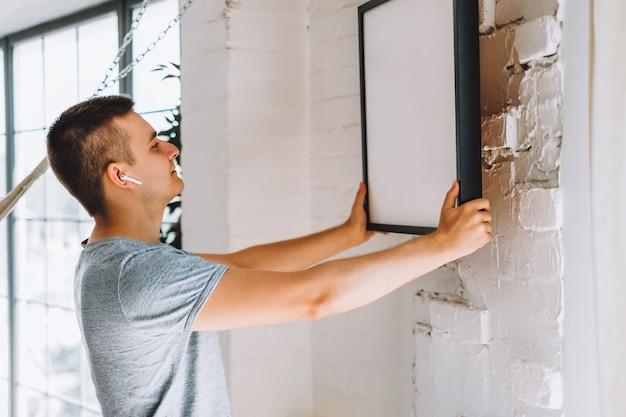 Beau jeune homme dans les écouteurs debout et accrocher une photo sur un mur de sone blanc dans la chambre