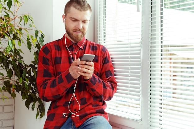 Beau, jeune homme, dans, écouteurs, tenue, téléphone portable