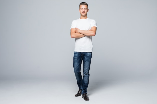 Beau jeune homme dans un t-shirt blanc de vêtements de style décontracté et un jean bleu sur blanc