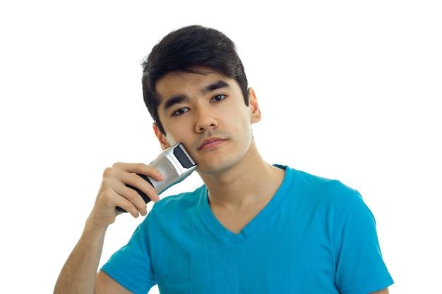 Beau jeune homme dans un t-shirt rase les machines à raser à l'aide d'isolement sur le mur blanc