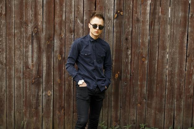 Beau jeune homme dans des vêtements élégants et des lunettes de soleil près d'un mur en bois vintage