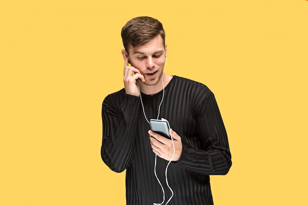 Beau jeune homme debout et écoutant de la musique.