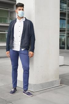 Beau jeune homme debout à l'extérieur dans le concept de coronavirus de masque médical
