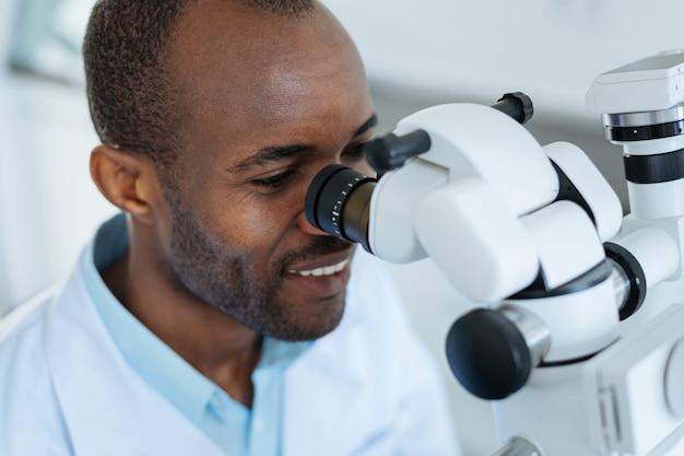 Beau jeune homme dentiste à la recherche dans l'objectif d'un microscope professionnel et souriant tout en l'utilisant pour l'examen de la cavité buccale
