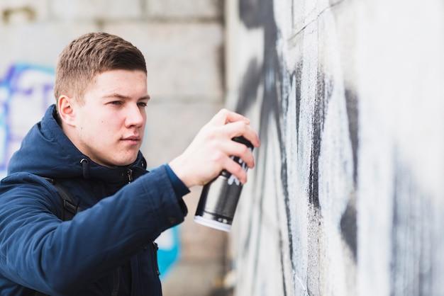 Beau jeune homme dessin graffiti avec un spray