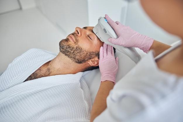 Beau jeune homme avec du chaume allongé sur un lit de repos tout en recevant un traitement facial au laser dans une armoire de cosmétologie