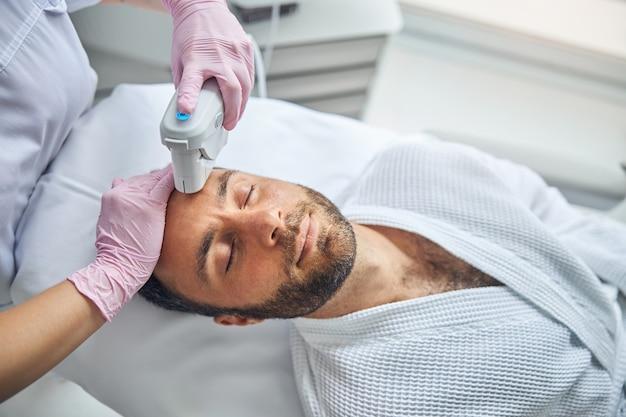 Beau jeune homme avec du chaume recevant un traitement facial au laser dans une clinique de bien-être