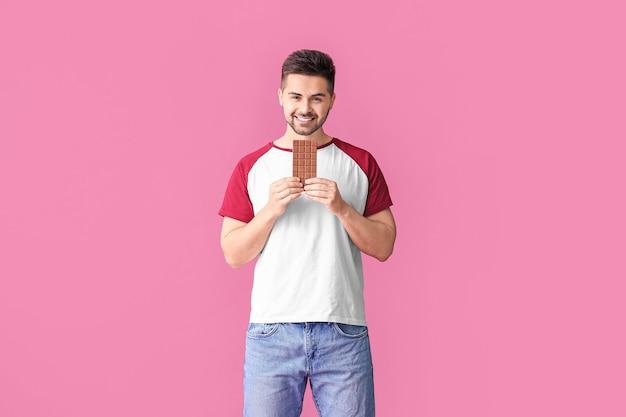 Beau jeune homme avec du chocolat savoureux sur fond de couleur