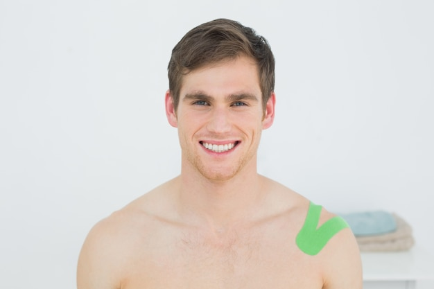 Beau jeune homme avec du ruban vert kinesio sur l'épaule