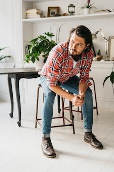 Beau jeune homme élégant assis sur un tabouret à la maison à la recherche de suite