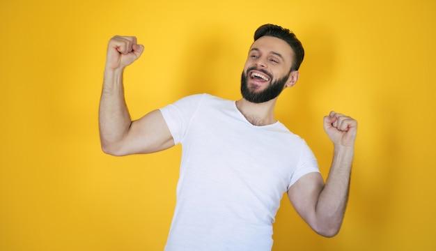 Beau jeune homme élégant barbu moderne excité pose avec un large sourire à pleines dents