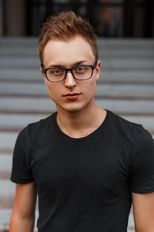Beau jeune homme élégant dans une chemise noire et des lunettes hipster.