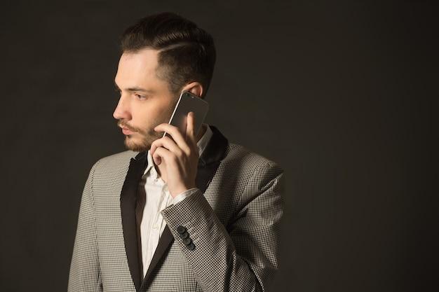Beau jeune homme élégant dans une veste avec un téléphone