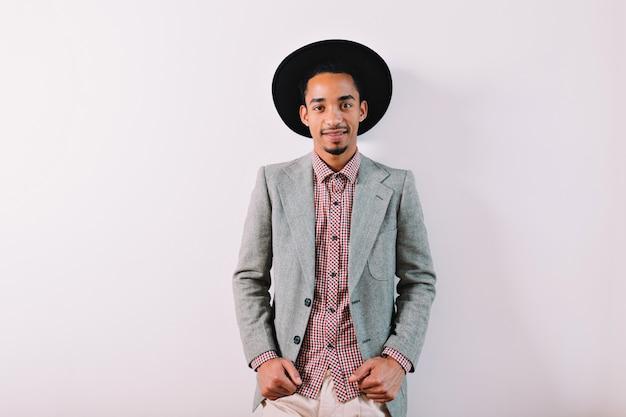 Beau jeune homme élégant porte chemise à carreaux chapeau noir et veste grise sur fond gris