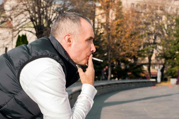 Beau jeune homme élégant qui fume à l'extérieur en milieu urbain, en détournant les yeux. bel homme blanc fumant une sigarette en plein air en journée ensoleillée