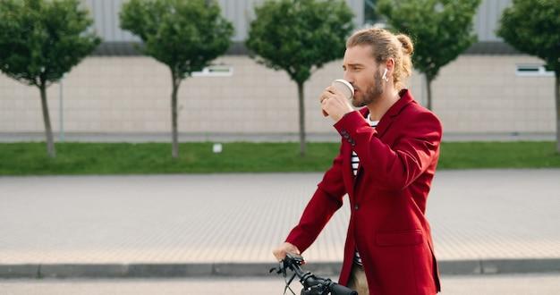 Beau jeune homme élégant de race blanche dans les écouteurs et veste rouge à cheval sur un scooter électrique dans la rue urbaine et boire du café. cavalier debout, sirotant un verre et allant en ville sur la route.