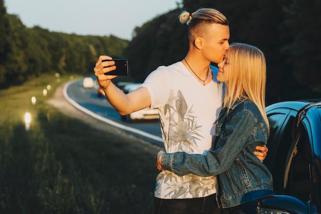 Beau jeune homme embrassant belle femme au front et à l'aide de smartphone pour prendre selfie en se tenant debout sur le bord de la route dans la campagne