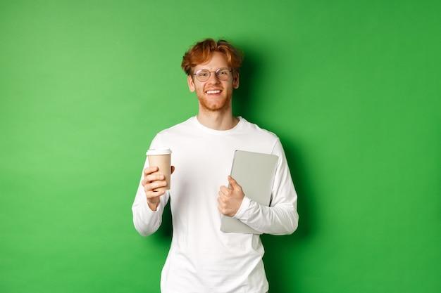 Beau jeune homme, employé avec ordinateur portable, boire du café en pause, souriant satisfait, debout sur fond vert.