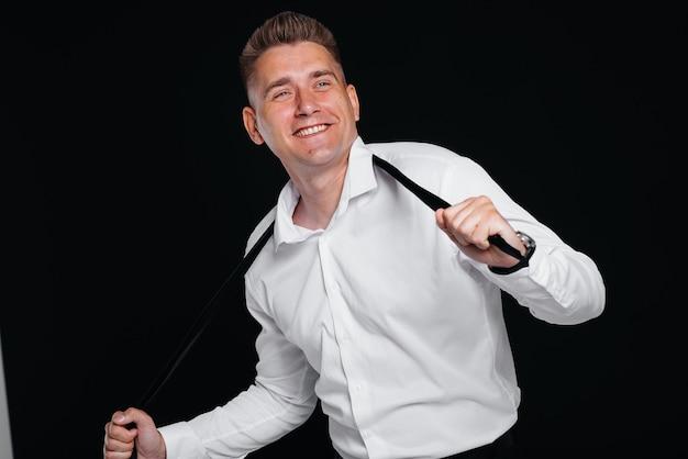 Un beau jeune homme enlève sa cravate et rit en posant sur un fond noir. un homme d'affaires élégant. un grand homme d'affaires.