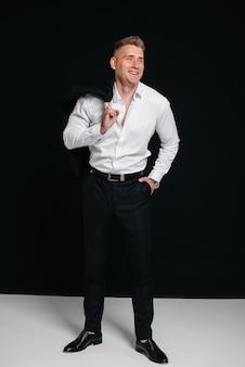 Un beau jeune homme enlève sa veste et rit en posant sur un fond noir. un homme d'affaires élégant. un grand homme d'affaires.