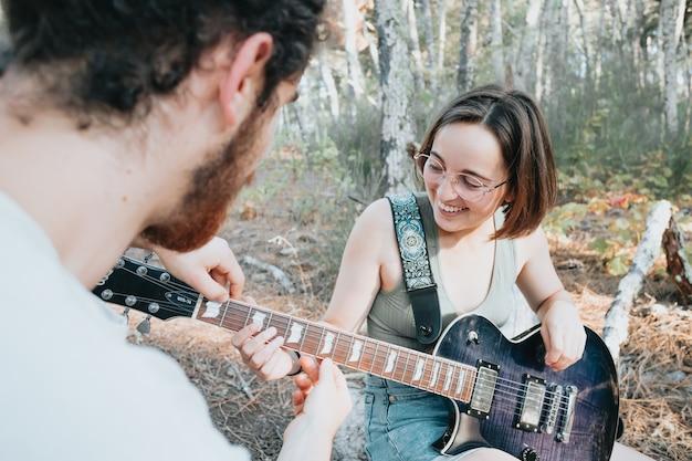 Beau jeune homme enseignant à une fille hipster à jouer de la guitare dans le parc. apprentissage et enseignement des concepts, passe-temps de la forêt et de la nature, temps libre