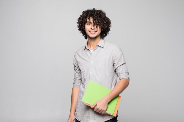 Beau jeune homme étudiant bouclé avec des cahiers sur isolé sur mur blanc