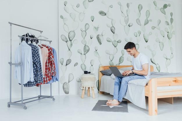 Beau jeune homme européen en vêtements décontractés souriant et utilisant un ordinateur portable assis sur le lit à la maison