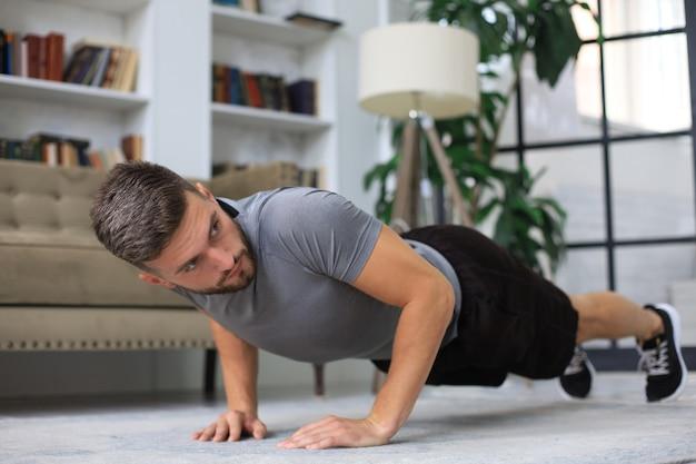 Beau jeune homme faisant des exercices de push up quotidiens à la maison.