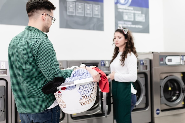 Beau jeune homme faisant la lessive à la laverie automatique.
