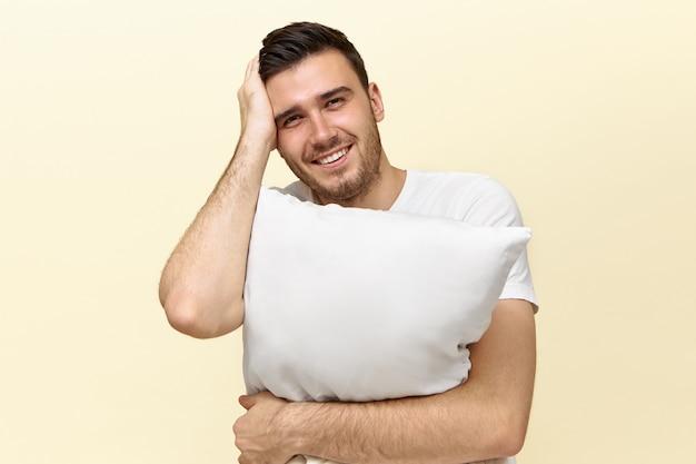 Beau jeune homme fatigué tenant un oreiller blanc