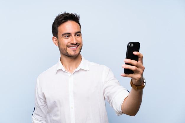 Beau jeune homme sur fond bleu isolé faisant un selfie