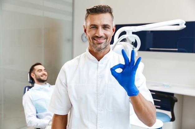 Beau jeune homme heureux médecin au centre de dentiste médical montrant le geste correct