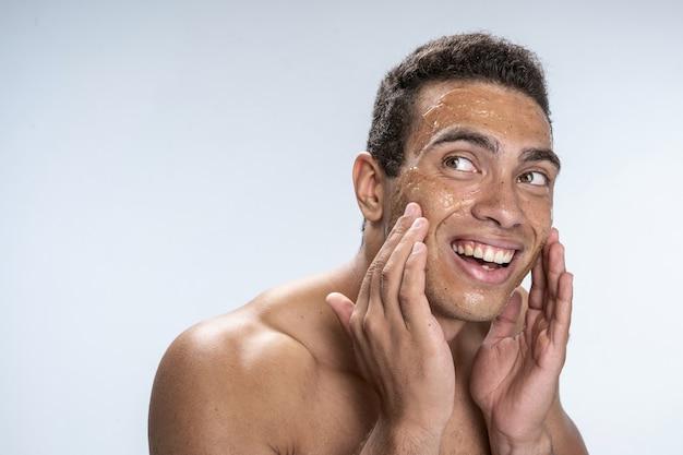 Beau jeune homme heureux de mettre un masque anti-humidité