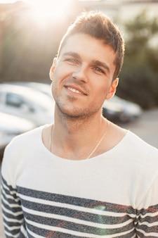 Beau jeune homme heureux avec un sourire debout au coucher du soleil.