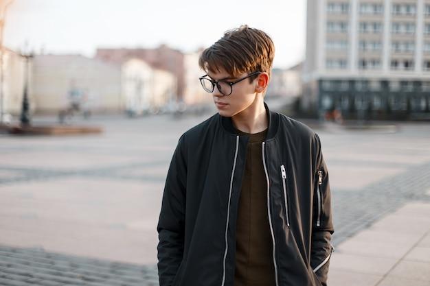 Beau jeune homme hipster dans des lunettes élégantes avec une coiffure à la mode dans une veste noire à la mode posant dans la rue un jour de printemps dans la ville. beau mec en vacances.