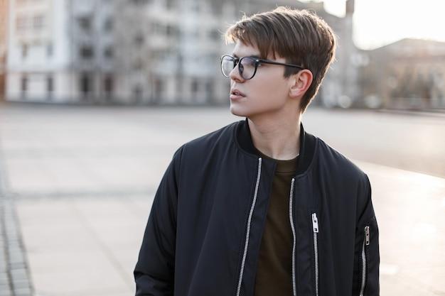 Beau jeune homme hipster dans des lunettes élégantes avec une coiffure à la mode dans un vêtement d'extérieur élégant dans la rue de la ville. attrayant gars élégant urbain.