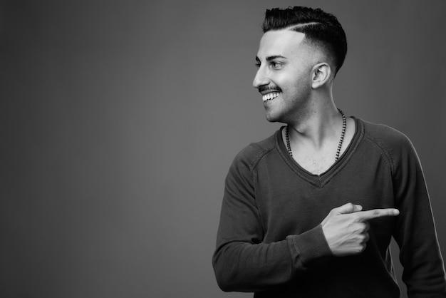 Beau jeune homme iranien avec moustache avec chemise à manches longues contre mur gris en noir et blanc