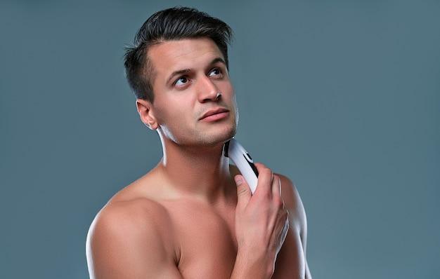 Beau jeune homme isolé. le portrait d'un homme musclé torse nu est debout sur un fond gris avec une tondeuse à la main pendant le rasage. concept de soins de l'homme.