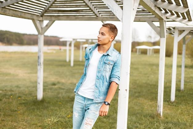 Beau jeune homme avec des jeans déchirés et une veste en jean près d'un auvent de plage en bois blanc en plein air