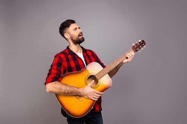 Beau jeune homme jouant de la guitare et chantant la chanson