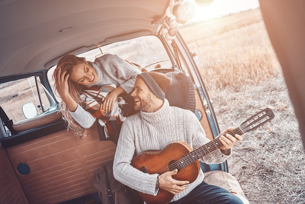 Beau jeune homme jouant de la guitare pour sa petite amie tout en passant du temps dans un camping-car